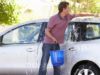 Man washing his car with bucket